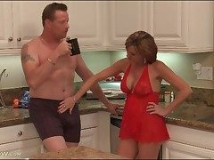 Housewife in underclothes blows the brush mendicant in kitchen