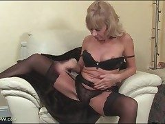 Mature ash-blonde Cathy Oakley unclothes to black lingerie